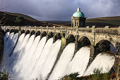 Elan Valley Dam in full flood-flow.  Early winter morning with low sun on dam and grey stormy clouds overhead.